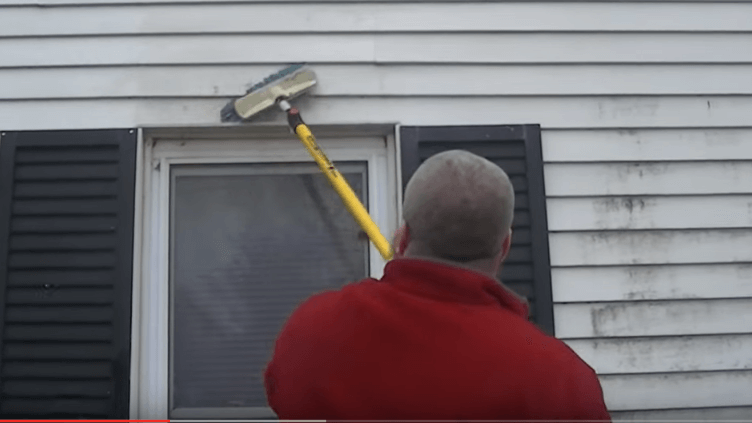 Man cleaning siding