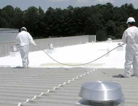 a chicago contractor applying coating to a metal roof