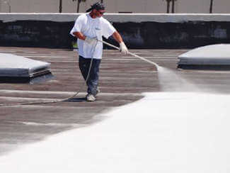 Worker Coating a roof with a sprayer